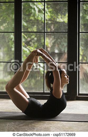 young attractive woman in dhanurasana pose studio