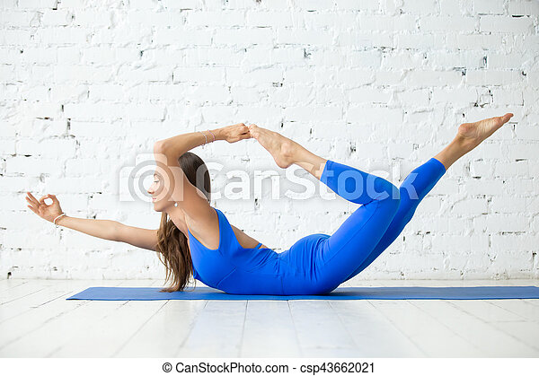 young attractive woman in dhanurasana pose white studio