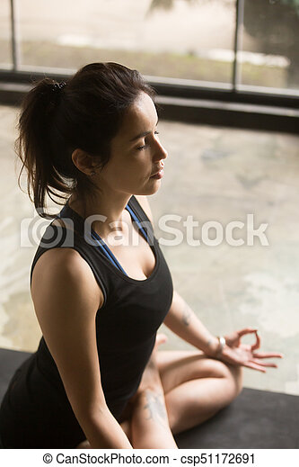 young attractive woman in lotus pose studio background