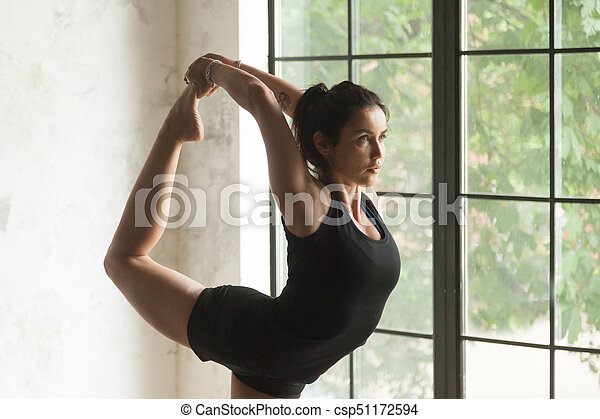 young attractive woman in natarajasana pose closeup