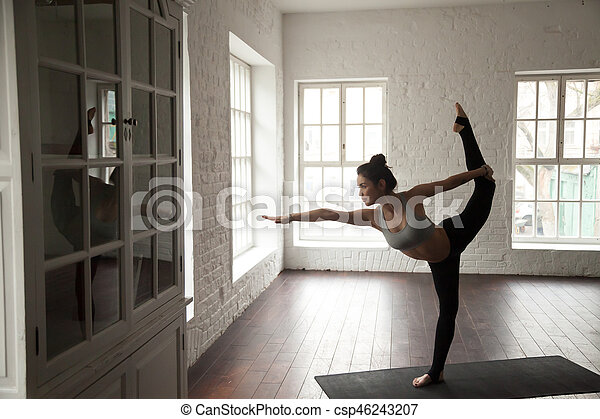 young attractive woman in natarajasana pose white loft