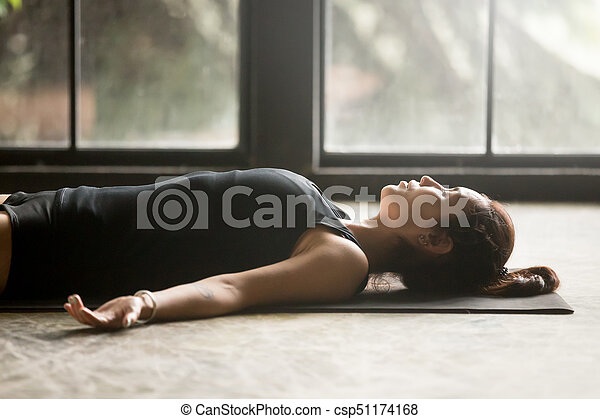 young attractive woman in savasana pose studio background