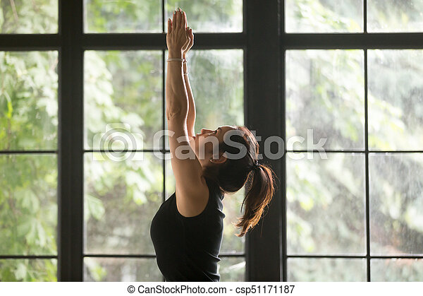 young attractive woman in tadasana pose window background