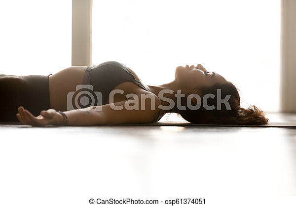 young attractive woman practicing yoga corpse pose close