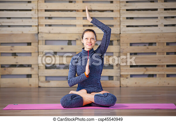 young attractive woman practicing yoga exercise lotus