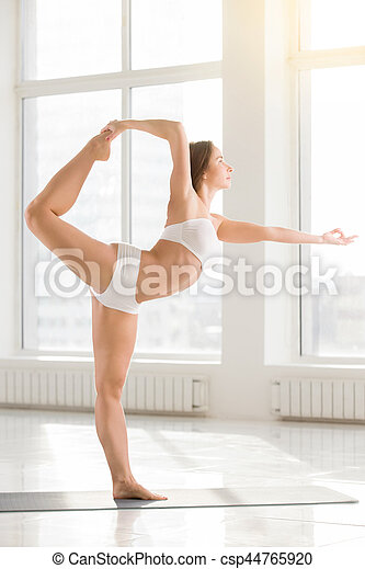 young attractive woman standing in natarajasana pose