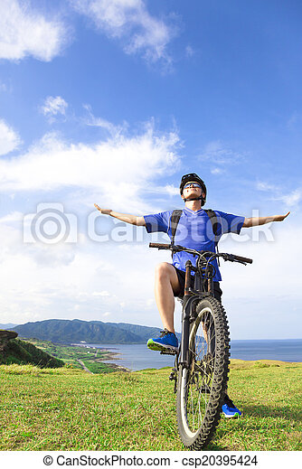 young backpacker sitting on a  mountain bike and relaxing pose - csp20395424