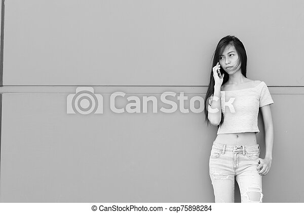 Young beautiful Asian teenage woman talking on mobile phone while standing and thinking against concrete wall outdoors - csp75898284