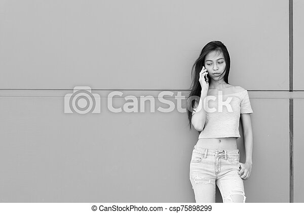 Young beautiful Asian teenage woman talking on mobile phone while thinking and looking down against concrete wall outdoors - csp75898299