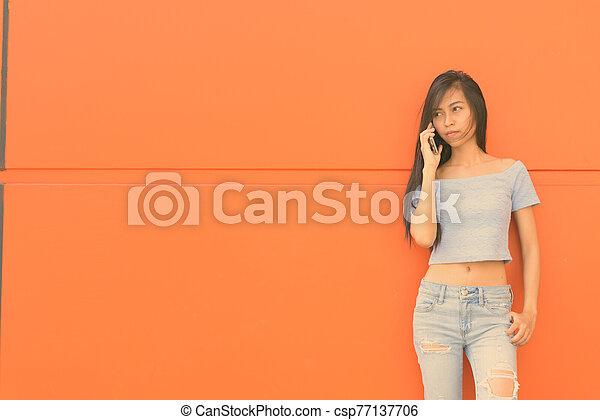 Young beautiful Asian teenage woman against orange wall - csp77137706