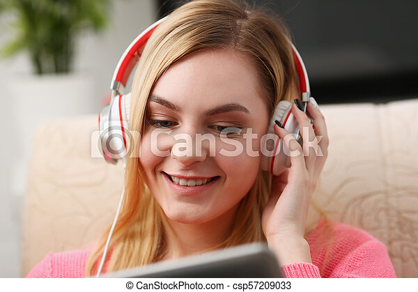 young beautiful blond woman sit on the sofa in livingroom hold tablet in arms listen to music - csp57209033