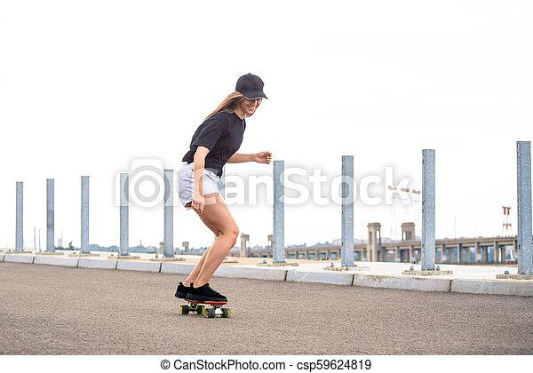 Young Beautiful Blonde Girl Riding Bright Skateboard on the Bridge - csp59624819