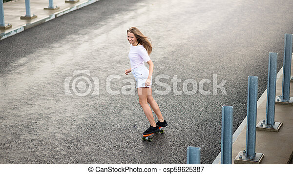 Young Beautiful Blonde Girl Riding Bright Skateboard on the Bridge - csp59625387