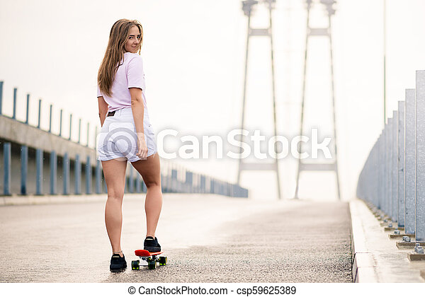 Young Beautiful Blonde Girl Riding Bright Skateboard on the Bridge - csp59625389