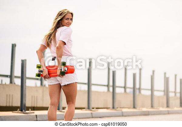 Young Beautiful Blonde Girl Riding Bright Skateboard on the Bridge - csp61019050