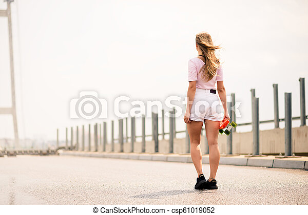 Young Beautiful Blonde Girl Riding Bright Skateboard on the Bridge - csp61019052