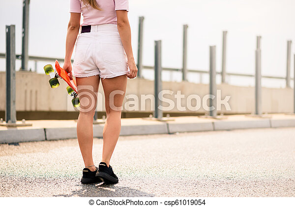 Young Beautiful Blonde Girl Riding Bright Skateboard on the Bridge - csp61019054