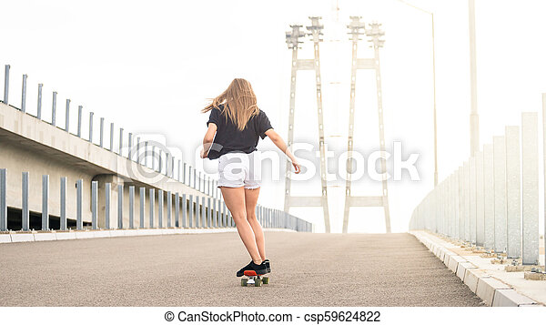 Young Beautiful Blonde Girl Riding Bright Skateboard on the Bridge - csp59624822