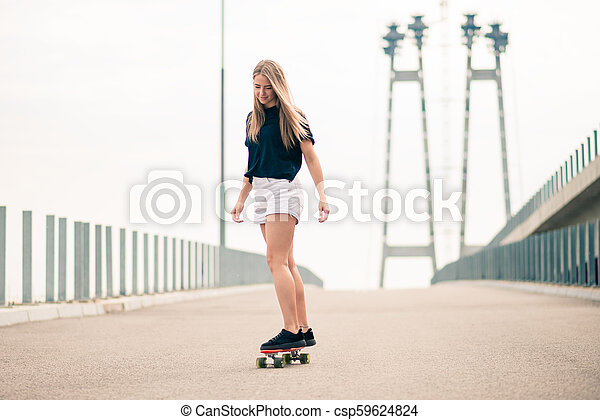 Young Beautiful Blonde Girl Riding Bright Skateboard on the Bridge - csp59624824