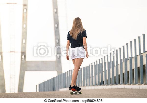Young Beautiful Blonde Girl Riding Bright Skateboard on the Bridge - csp59624826