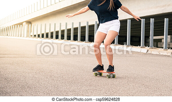 Young Beautiful Blonde Girl Riding Bright Skateboard on the Bridge - csp59624828
