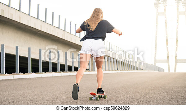 Young Beautiful Blonde Girl Riding Bright Skateboard on the Bridge - csp59624829