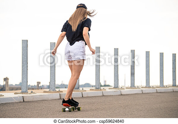 Young Beautiful Blonde Girl Riding Bright Skateboard on the Bridge - csp59624840