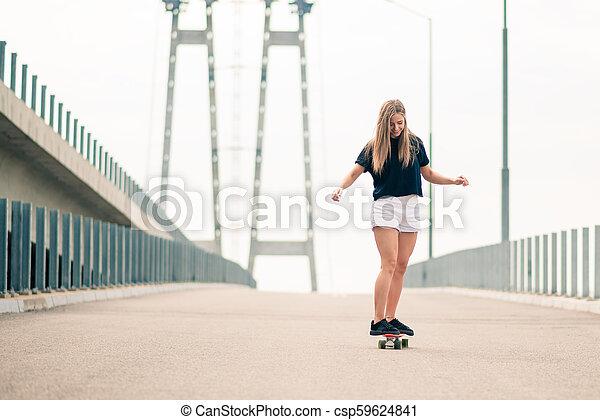Young Beautiful Blonde Girl Riding Bright Skateboard on the Bridge - csp59624841