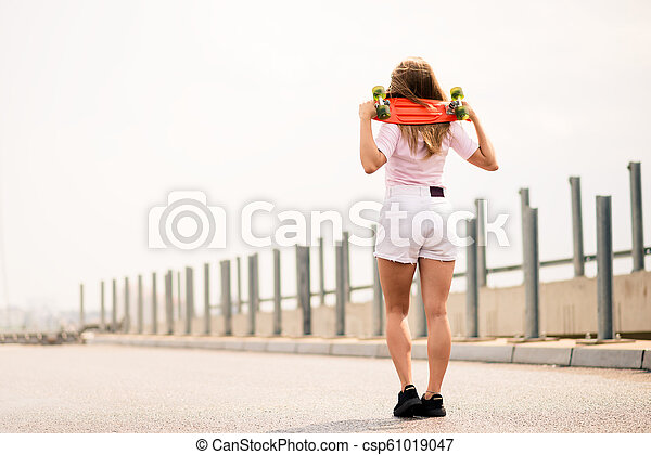 Young Beautiful Blonde Girl Riding Bright Skateboard on the Bridge - csp61019047