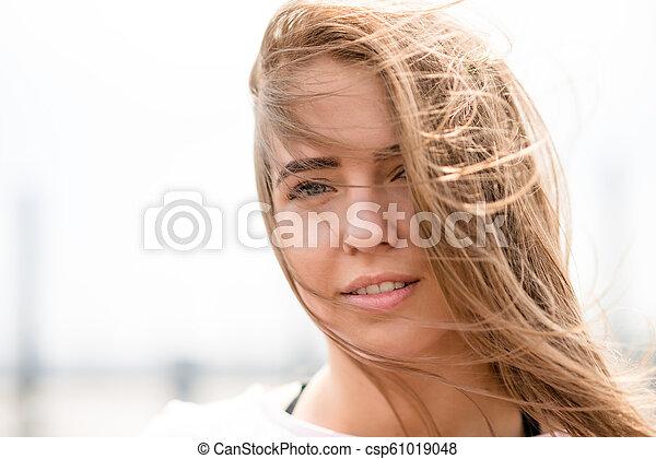 Young Beautiful Blonde Girl Riding Bright Skateboard on the Bridge - csp61019048