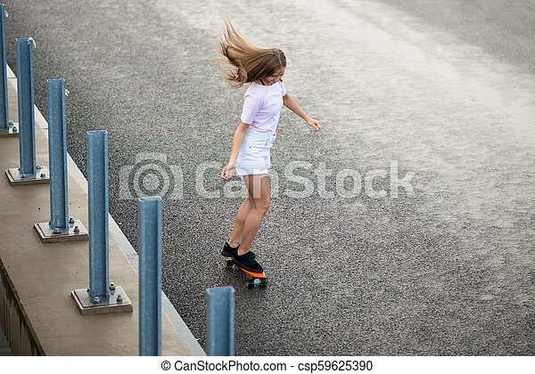 Young Beautiful Blonde Girl Riding Bright Skateboard on the Bridge - csp59625390