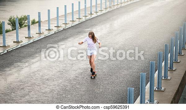 Young Beautiful Blonde Girl Riding Bright Skateboard on the Bridge - csp59625391