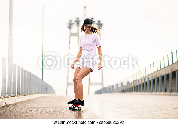 Young Beautiful Blonde Girl Riding Bright Skateboard on the Bridge - csp59625392
