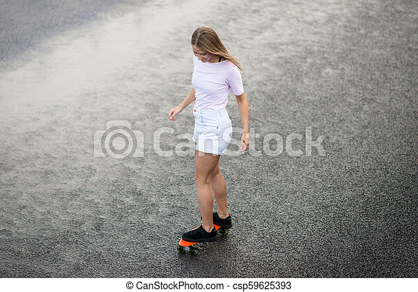 Young Beautiful Blonde Girl Riding Bright Skateboard on the Bridge - csp59625393