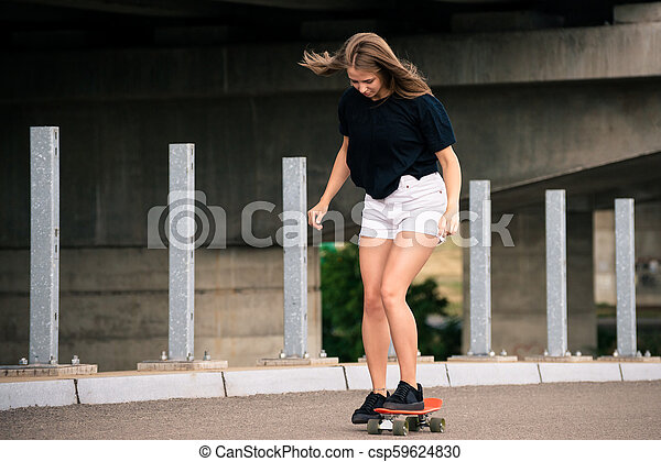Young Beautiful Blonde Girl Riding Bright Skateboard on the Bridge - csp59624830