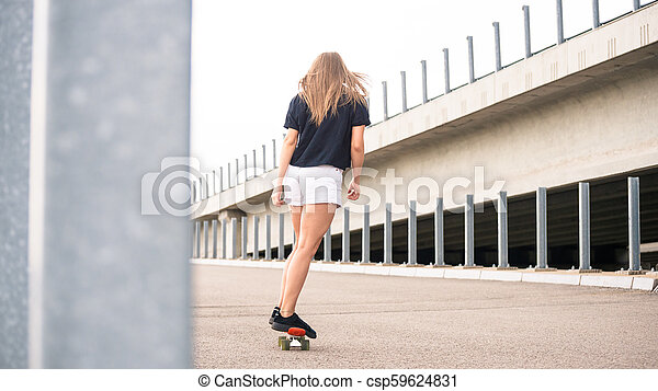 Young Beautiful Blonde Girl Riding Bright Skateboard on the Bridge - csp59624831