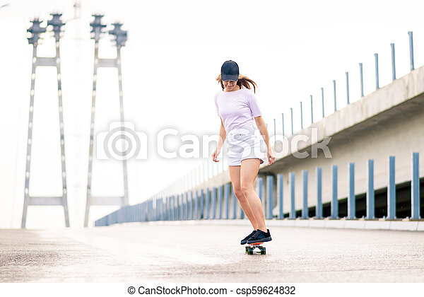 Young Beautiful Blonde Girl Riding Bright Skateboard on the Bridge - csp59624832