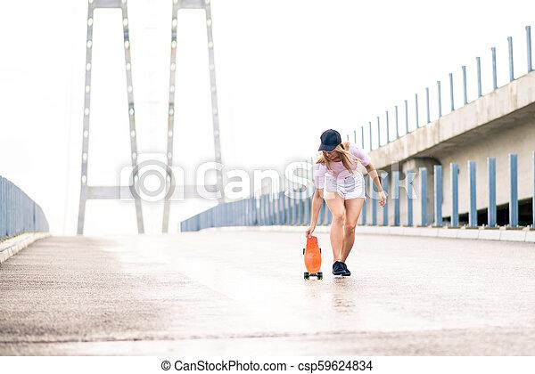 Young Beautiful Blonde Girl Riding Bright Skateboard on the Bridge - csp59624834