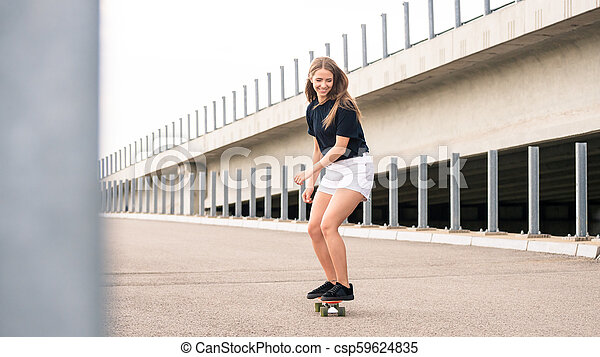 Young Beautiful Blonde Girl Riding Bright Skateboard on the Bridge - csp59624835