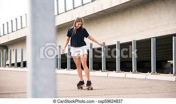 Young Beautiful Blonde Girl Riding Bright Skateboard on the Bridge - csp59624837