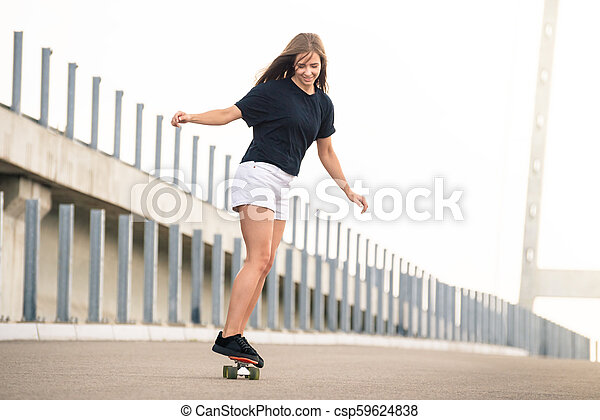 Young Beautiful Blonde Girl Riding Bright Skateboard on the Bridge - csp59624838