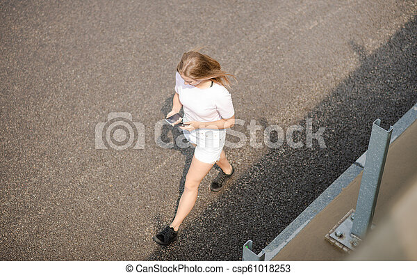 Young Beautiful Blonde Girl Using Smartphone while Walking on the Road - csp61018253