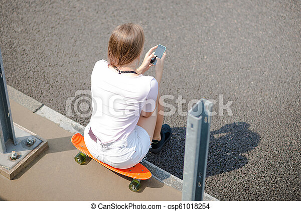 Young Beautiful Blonde Girl Using Smartphone while Sitting on the Skateboard - csp61018254