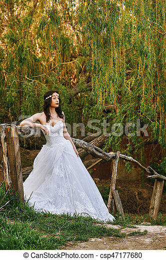 Young beautiful bride in the flowered garden . Wedding day - csp47177680