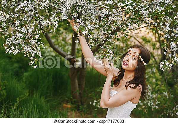 Young beautiful bride in the flowered garden . Wedding day - csp47177683