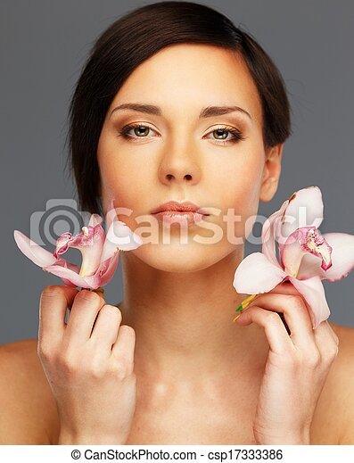 Young beautiful brunette woman with orchid flowers  - csp17333386