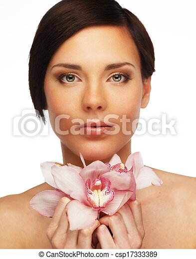 Young beautiful brunette woman with orchid flowers  - csp17333389