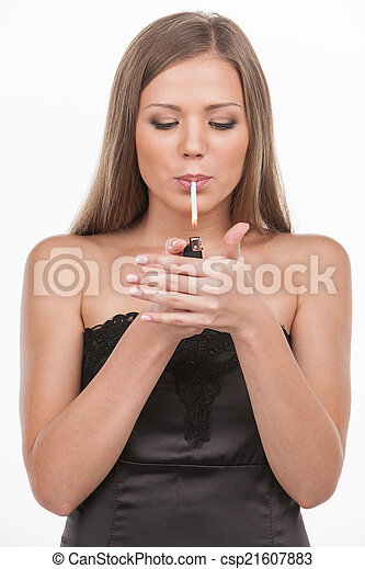 young beautiful girl inhaling smoke. brunette lighting cigarette on white background - csp21607883