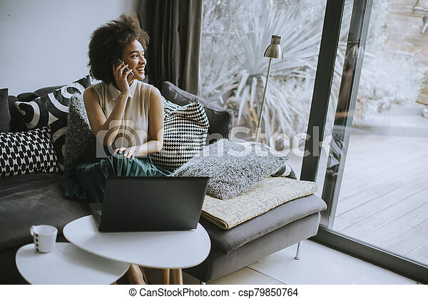 Young beautiful lady with curly hair work on the notebook while sit down on the couch at home - csp79850764