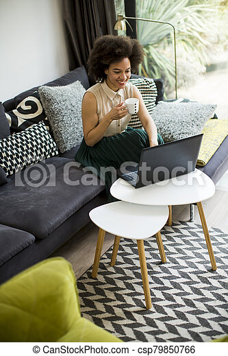 Young beautiful lady with curly hair work on the notebook while sit down on the couch at home - csp79850766